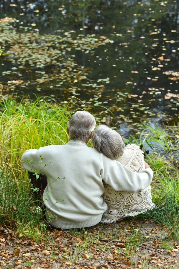Retrato de los pares mayores que se sientan cerca del lago en oto?o imagen de archivo libre de regalías