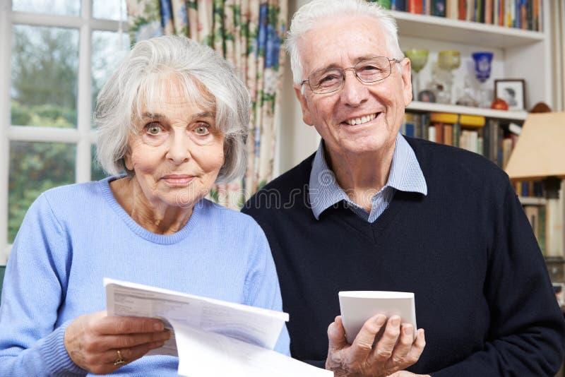 Retrato de los pares mayores sonrientes que revisan a casa finanzas fotografía de archivo libre de regalías