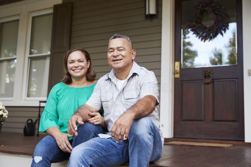 Retrato de los pares mayores sonrientes que se sientan en Front Of Their Home imagenes de archivo