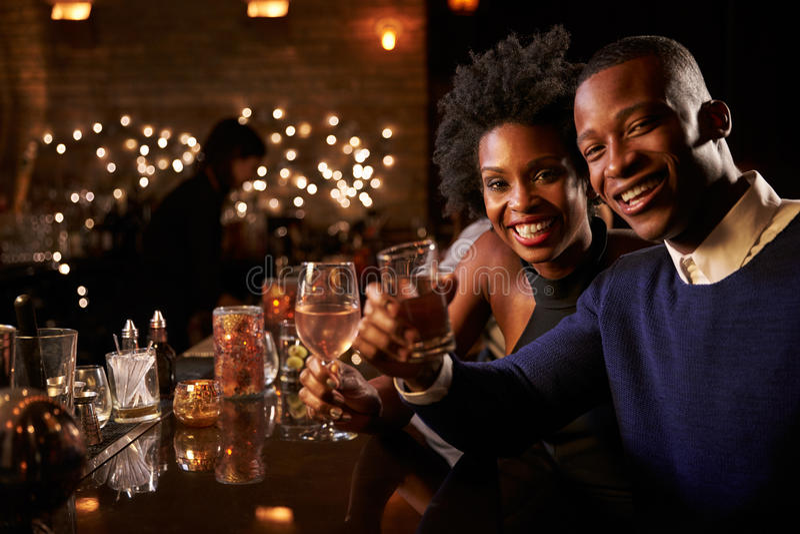 Retrato de los pares que disfrutan de noche hacia fuera en la barra del cóctel imagen de archivo