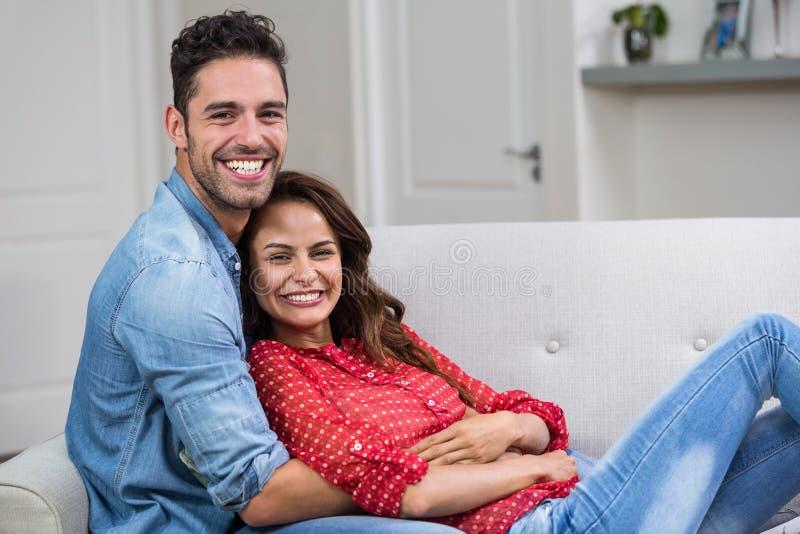 Retrato de los pares románticos que abrazan en el sofá fotos de archivo libres de regalías