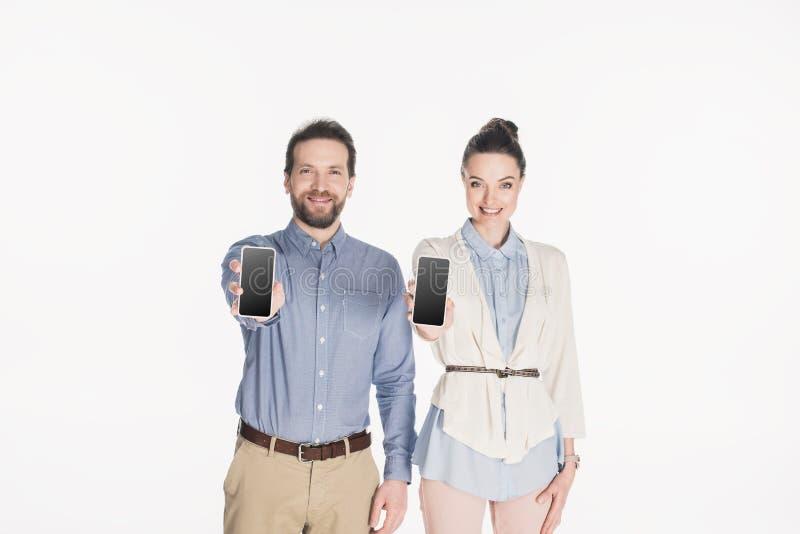 retrato de los pares sonrientes que muestran smartphones con las pantallas en blanco en manos fotografía de archivo libre de regalías