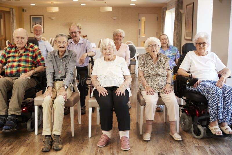 Retrato de los residentes mayores de la casa de retiro que se sientan en salón foto de archivo libre de regalías