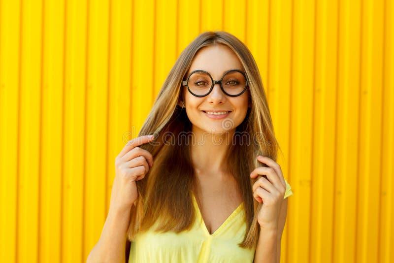 Retrato de los vidrios divertidos de un juguete de la muchacha que llevan alegre que miran para arriba o foto de archivo