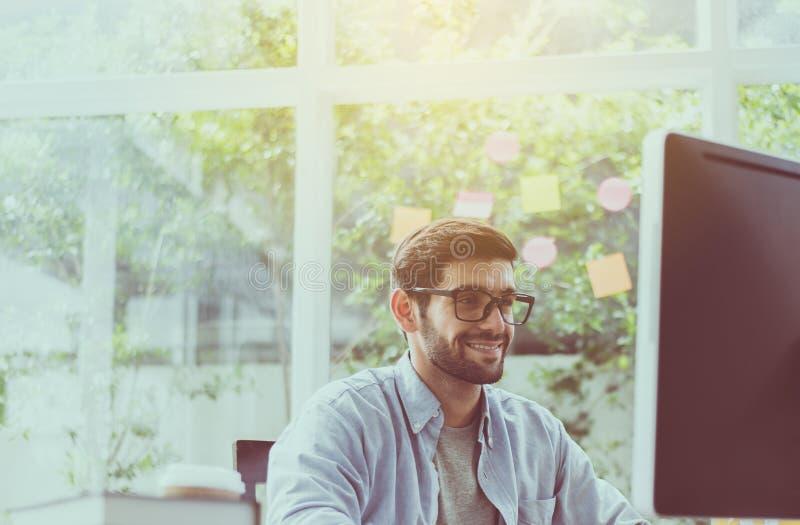 Retrato de los vidrios que llevan del hombre hermoso con la barba mientras que trabaja en línea en casa, feliz y la sonrisa fotografía de archivo libre de regalías