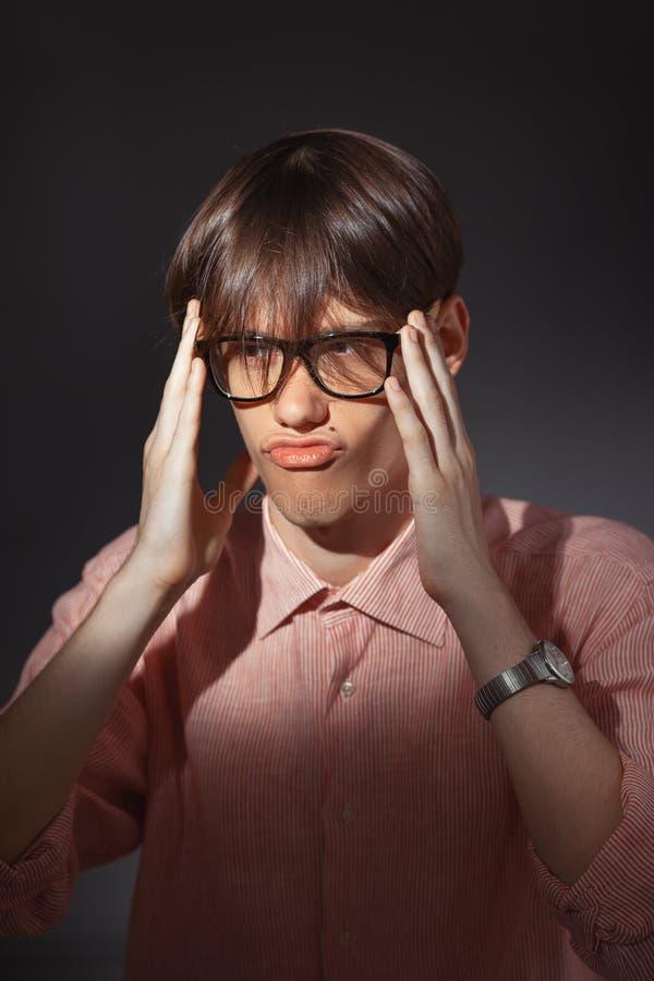Retrato de los vidrios que llevan desconcertados del hombre caucásico joven divertido, camisa en una tira que localiza dentro co fotografía de archivo libre de regalías