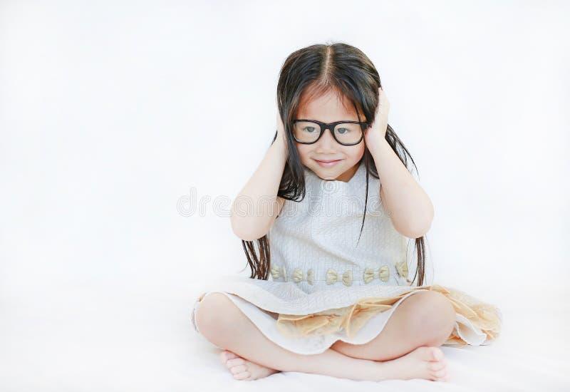 Retrato de los vidrios que llevan de la pequeña muchacha asiática del niño contra el fondo blanco fotos de archivo