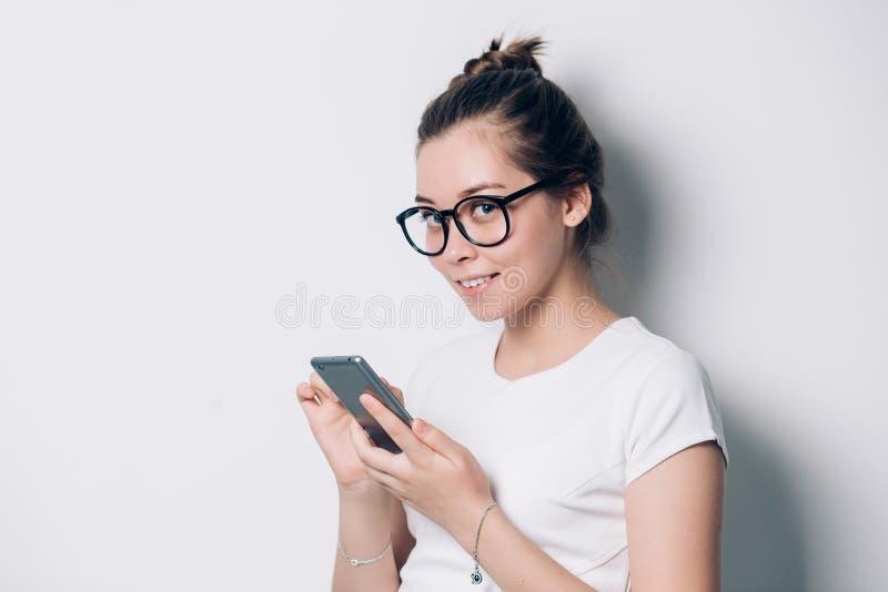 Retrato de los vidrios que llevan sonrientes felices de la mujer joven usando smartphone en el fondo blanco imagenes de archivo
