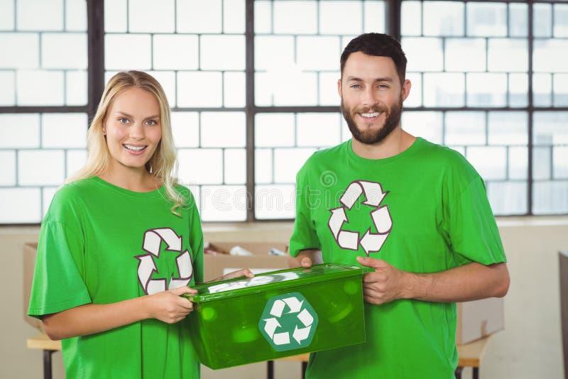 Retrato de los voluntarios sonrientes que llevan reciclando el envase imágenes de archivo libres de regalías