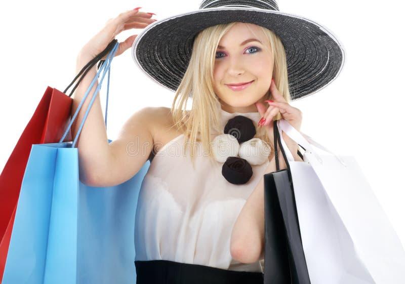 Retrato de louro no chapéu com sacos de compra imagens de stock