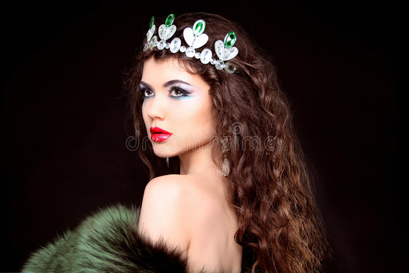 Retrato de lujo de la mujer hermosa con el pelo largo en abrigo de pieles. Jewe imagen de archivo
