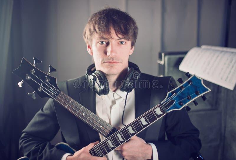 Retrato de músico en estudio con dos guitarras imagen de archivo libre de regalías