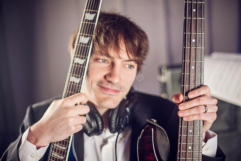 Retrato de músico en estudio con dos guitarras fotos de archivo