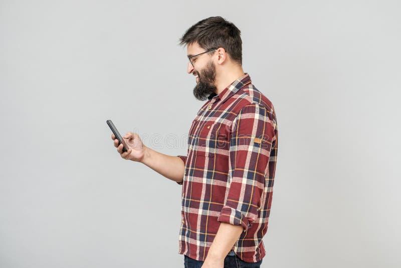 Retrato de mandar un SMS europeo hermoso del rato del teléfono de la tenencia del hombre fotografía de archivo libre de regalías