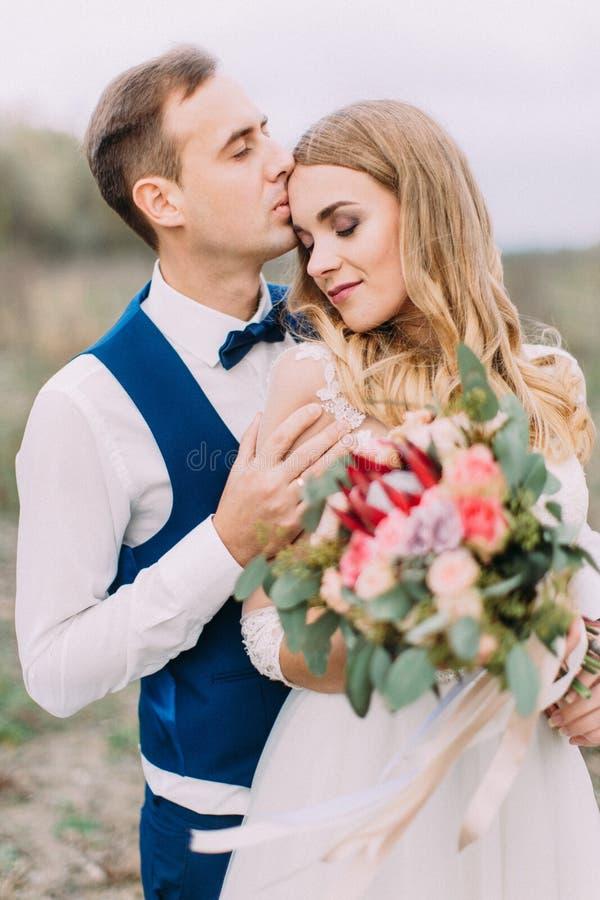 Retrato de medio cuerpo del novio que besa a la novia en la frente La novia sostiene el ramo de la boda foto de archivo libre de regalías