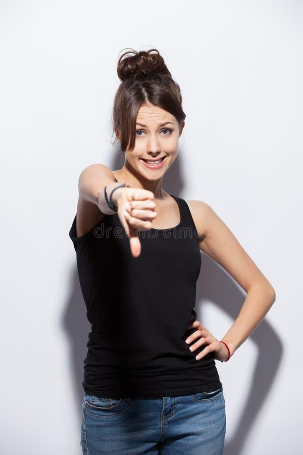 Retrato de medio cuerpo de la mujer que manosea con los dedos abajo, aislado en blanco fotografía de archivo