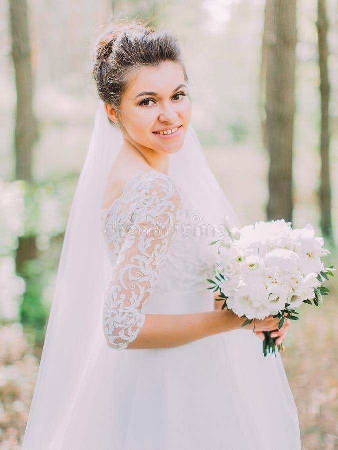 Retrato de medio cuerpo de la novia alegre con el ramo de la boda de peonías La ubicación del bosque foto de archivo libre de regalías