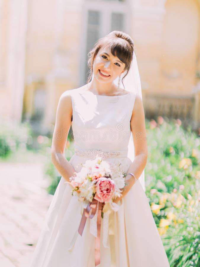 Retrato de medio cuerpo de la novia sonriente hermosa que sostiene el ramo de la boda de peonías rosadas imagen de archivo