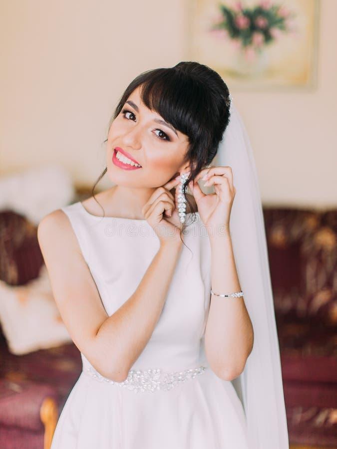 Retrato de medio cuerpo de la novia sonriente que pone los pendientes fotografía de archivo libre de regalías