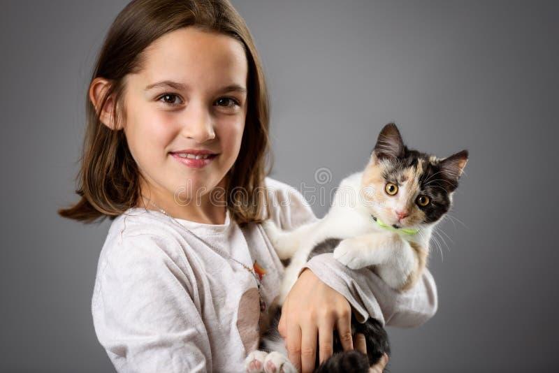 Retrato de menina feliz com o gatinho calico foto de stock
