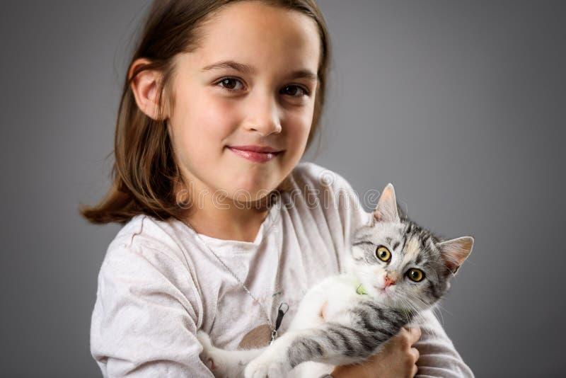 Retrato de menina feliz com o gatinho calico fotografia de stock royalty free