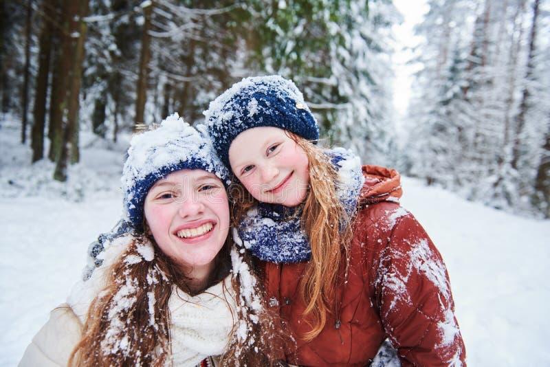 Retrato de meninas de sorriso felizes na floresta nevado do inverno foto de stock royalty free