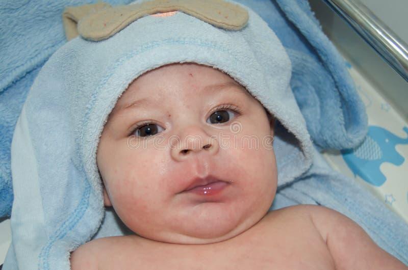 Retrato de 4 meses bonitos do bebê idoso com a toalha azul em sua cabeça após o banho foto de stock