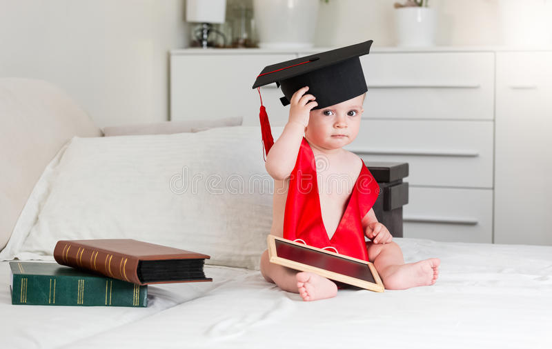 Retrato de 10 meses del bebé con los libros que llevan la graduación fotografía de archivo libre de regalías