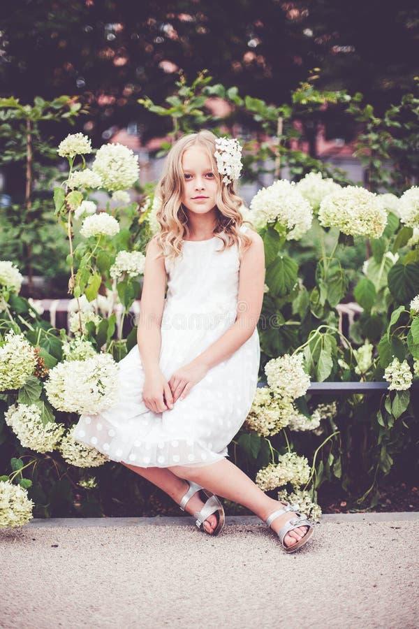 Retrato de moda de una hermosa sonriente de 9-10 años posando contra flores de horangea florecientes imagen de archivo libre de regalías