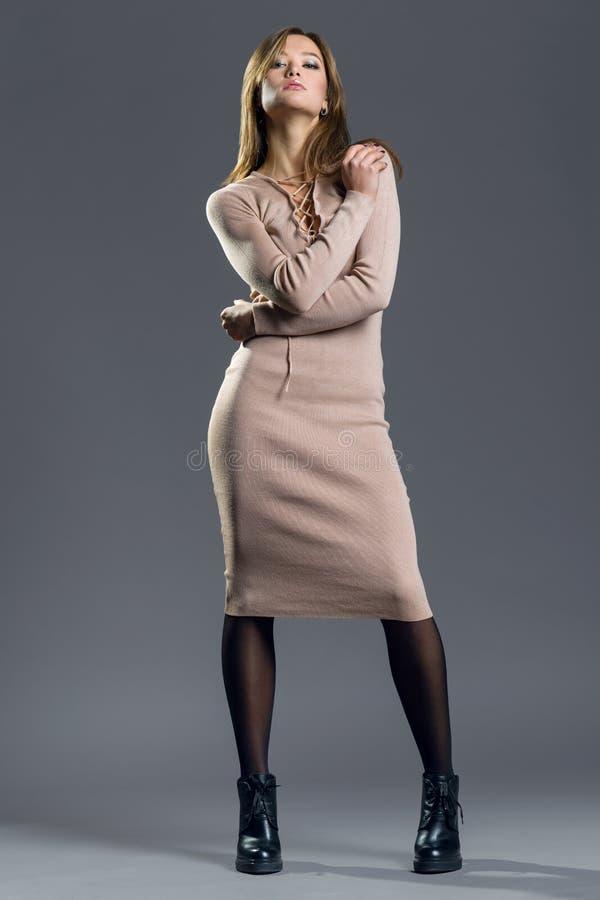 Retrato de moda de una muchacha elegante en un vestido desnudo apretado hecho punto en un fondo gris foto de archivo libre de regalías