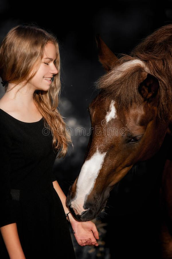 Retrato de moda de una mujer joven y de un caballo hermosos foto de archivo libre de regalías