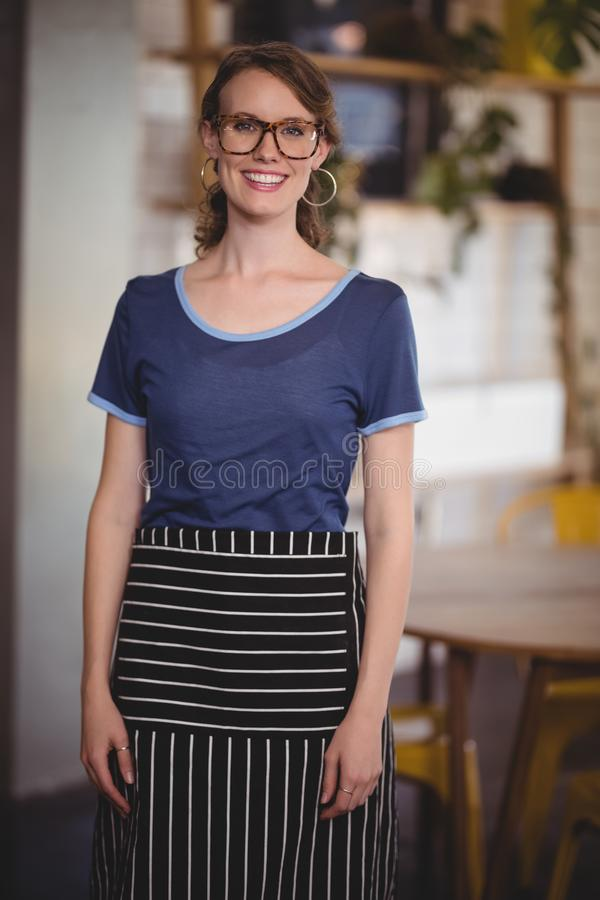 Retrato de monóculos vestindo de sorriso da empregada de mesa nova na cafetaria imagem de stock royalty free