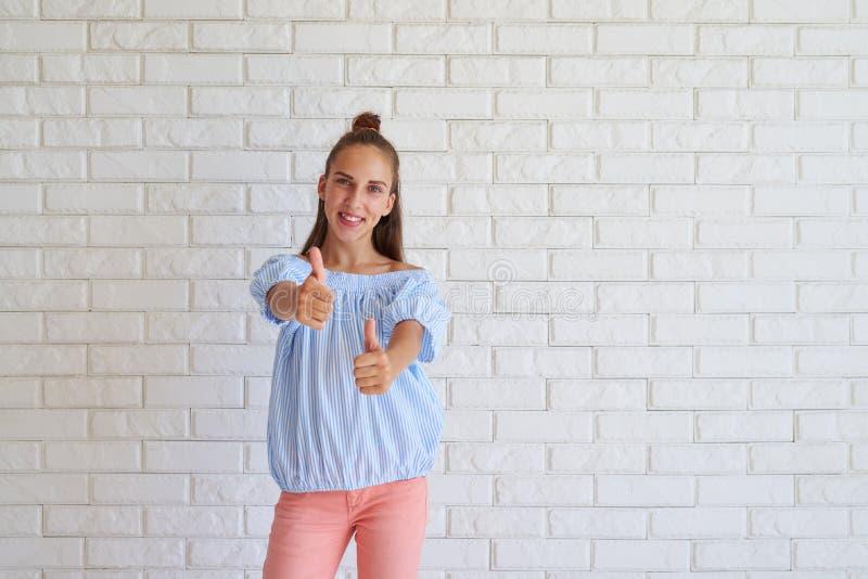 Retrato de mostrar novo da fêmea polegares acima fotografia de stock