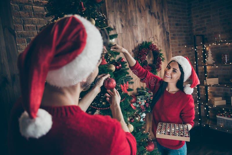 Retrato de mujer romántica sosteniendo una colección de baubles decora un árbol de Navidad verde que mira a su marido foto de archivo