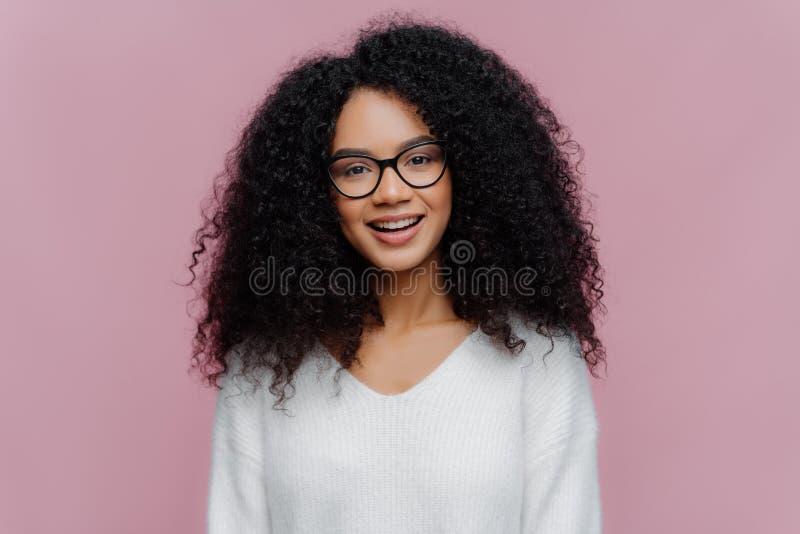 Retrato de mujer sonriente de aspecto agradable con peinado afro, con gafas ópticas y suéter blanco, tiene cara alegre imagen de archivo