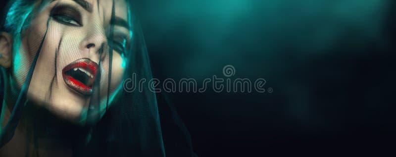 Retrato de mujer vampiro de Halloween con velo negro en la cara. Bella Sexy Vampiro Chica con dientes, labios rojos sangrientos. m imagen de archivo