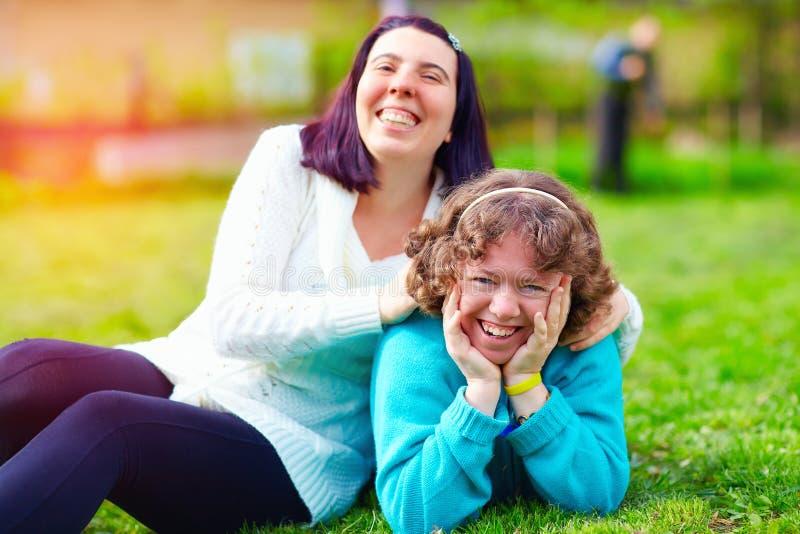 Retrato de mujeres felices con incapacidad en césped de la primavera imagenes de archivo