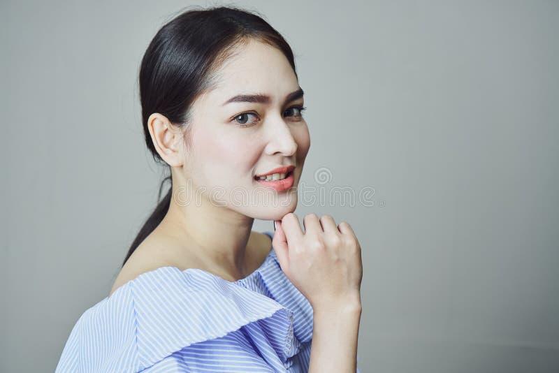 Retrato de mujeres jovenes asiáticas sonrientes en gris un fondo da una luz suave imágenes de archivo libres de regalías
