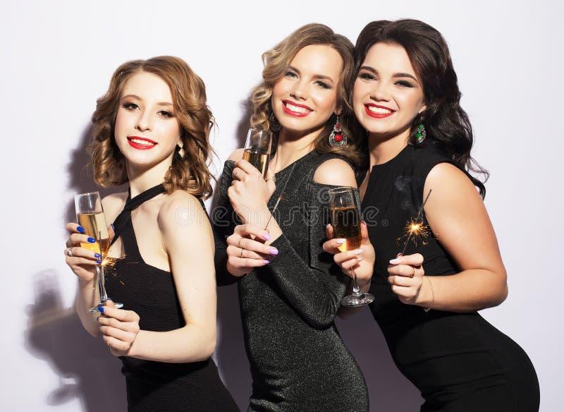Retrato de mujeres jovenes elegantes con los vidrios de un champán en la celebración fotografía de archivo