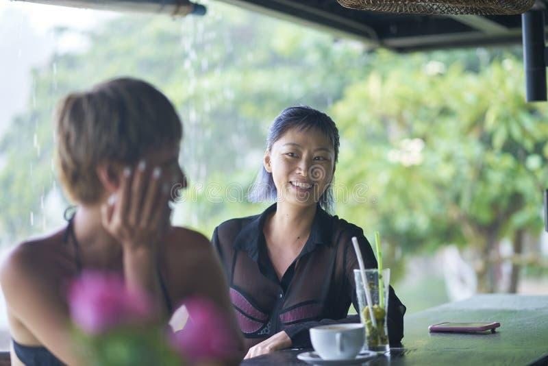Retrato de 2 mulheres asiáticas que conversam, bebendo & sorrindo na barra da praia no verão foto de stock royalty free