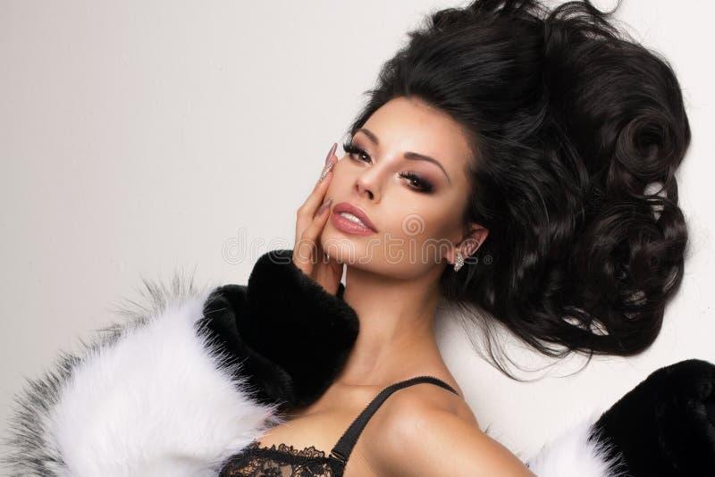 Retrato de mulheres elegantes do brunnette no estúdio que encontra-se sobre o fundo branco que veste a roupa interior, meias e a  foto de stock royalty free