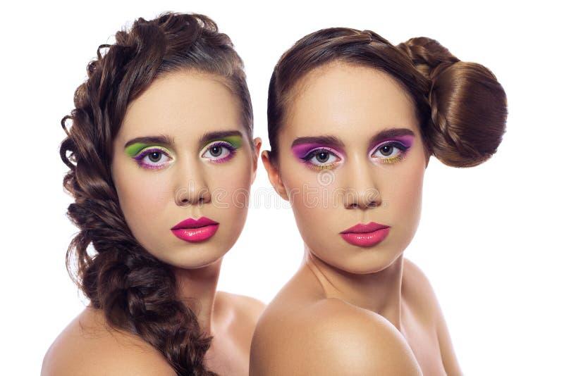 Retrato de mulheres novas da forma dos gêmeos bonitos com penteado e composição verde cor-de-rosa vermelha Isolado no fundo branc fotografia de stock