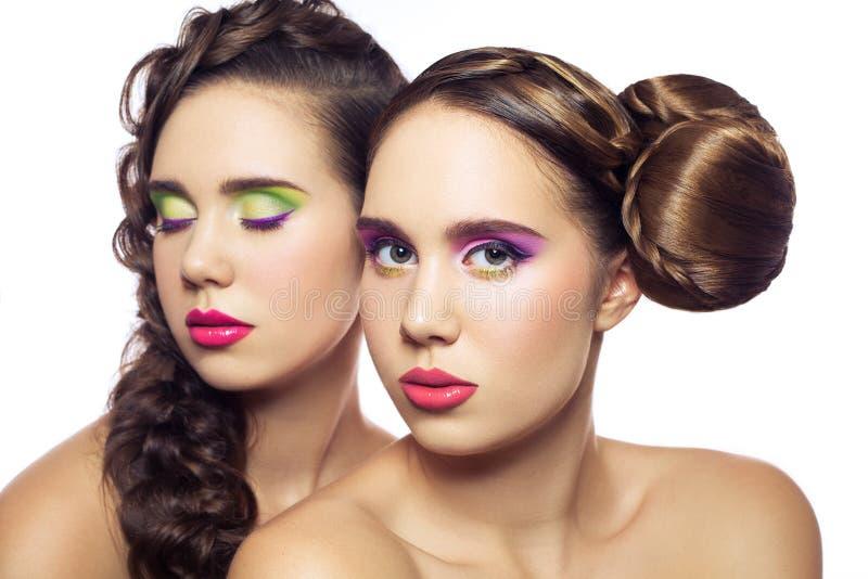 Retrato de mulheres novas da forma dos gêmeos bonitos com penteado e composição verde cor-de-rosa vermelha Isolado no fundo branc imagens de stock royalty free