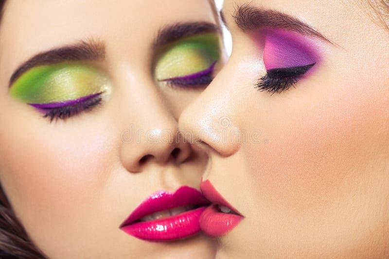 Retrato de mulheres novas da forma dos gêmeos bonitos com penteado e composição verde cor-de-rosa vermelha Isolado no fundo branc imagem de stock