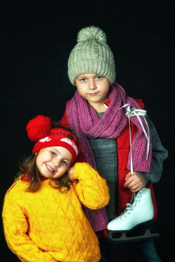 Retrato de niños en suéteres calientes en un fondo oscuro imágenes de archivo libres de regalías