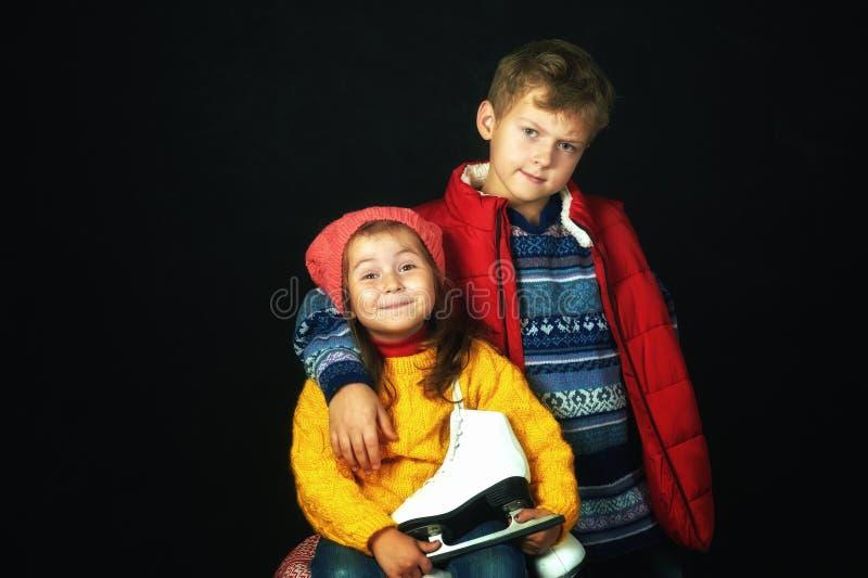 Retrato de niños en suéteres calientes en un fondo oscuro imagenes de archivo
