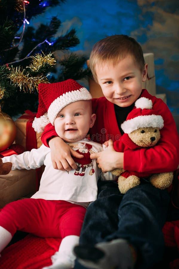 Retrato de niños felices con las cajas y las decoraciones de regalo de la Navidad Dos niños que se divierten en casa imagenes de archivo