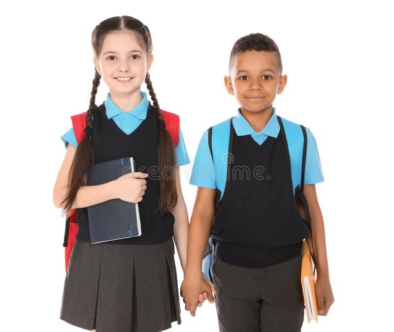 Retrato de ni?os lindos en uniforme escolar con los libros en blanco foto de archivo libre de regalías
