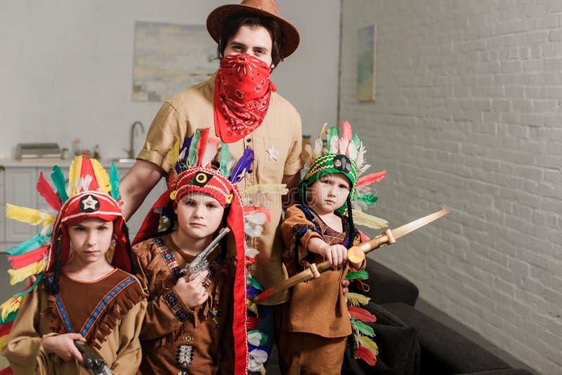 retrato de niños pequeños en trajes y padre indígenas en sombrero y del pañuelo rojo que mira la cámara imágenes de archivo libres de regalías