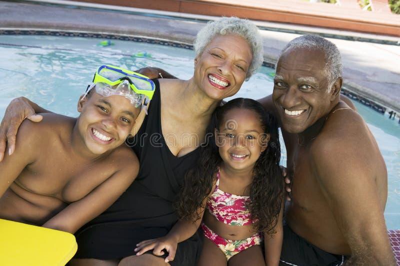 Retrato de nietos con los abuelos por la piscina fotos de archivo